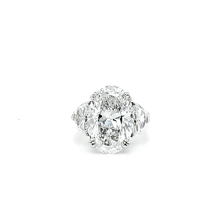Center Stone is 6.16 carat Oval Cut Diamond with a D color and SI2 clarity. Side stones are Half Moon shaped diamonds weighing 1.02 carats total and a similar color and clarity to the center stone. Set in a platinum ring. The Center stone has strong
