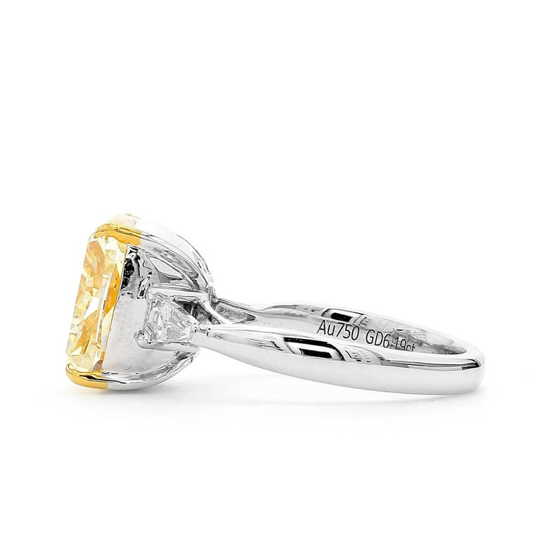Natural, untreated 6.19 carat main light yellow diamond, surrounded by smaller white diamonds making up a total of 6.56 Carats. Cushion Shape. This piece has been expertly crafted using 18 Karat White Gold.   This piece can be adjusted or resized.
