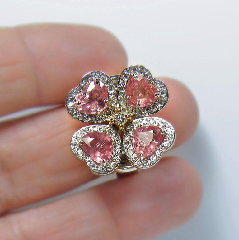 This Stunning GIA certified Padparadscha Sapphire flower ring is set with four heart cut sapphire Padparadscha, weighing over 5.20 carats. Average color/clarity Sapphire: Pinkish-Orange/ VS. These gorgeous sapphires are accented with 1.00 carat of