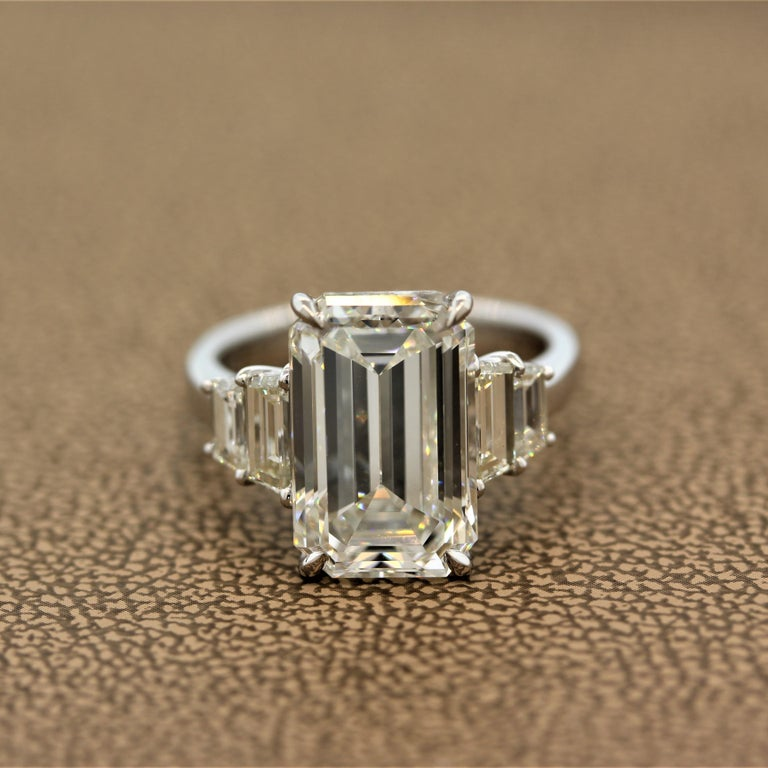 A chic and fashionable engagement ring featuring a 6.40 carat emerald cut diamond graded by the GIA as J color and VVS2 in clarity. We believe this rating to be harsh as in the faceup position this diamond looks 1-2 color grades better. Close to