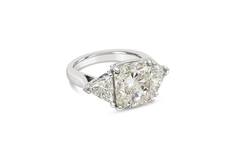 A classic and brilliant engagement ring style showcasing a beautiful 6.90 carat radiant cut diamond, flanked by trillion cut diamonds weighing 1.50 carats total. GIA certified the center diamond as L color, SI1 clarity. Set in a polished platinum