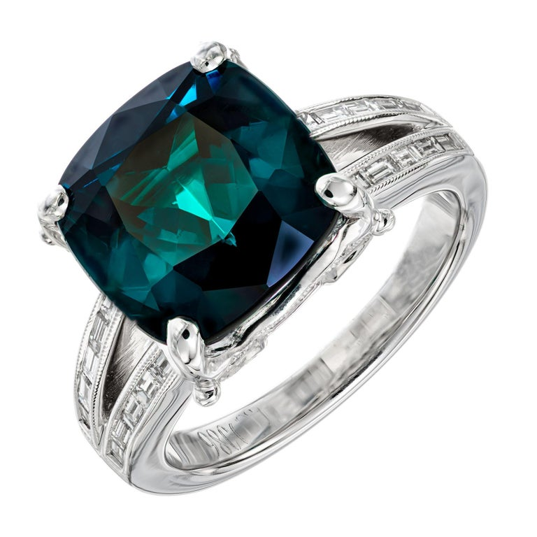 GIA Certified natural green blue 6.90 carat cushion cut tourmaline in a custom-made platinum ring set with 20 baguette and 36 round accent diamonds.  1 cushion cut greenish blue tourmaline, approx. 6.90 Carats GIA Certificate # 2213379527 20