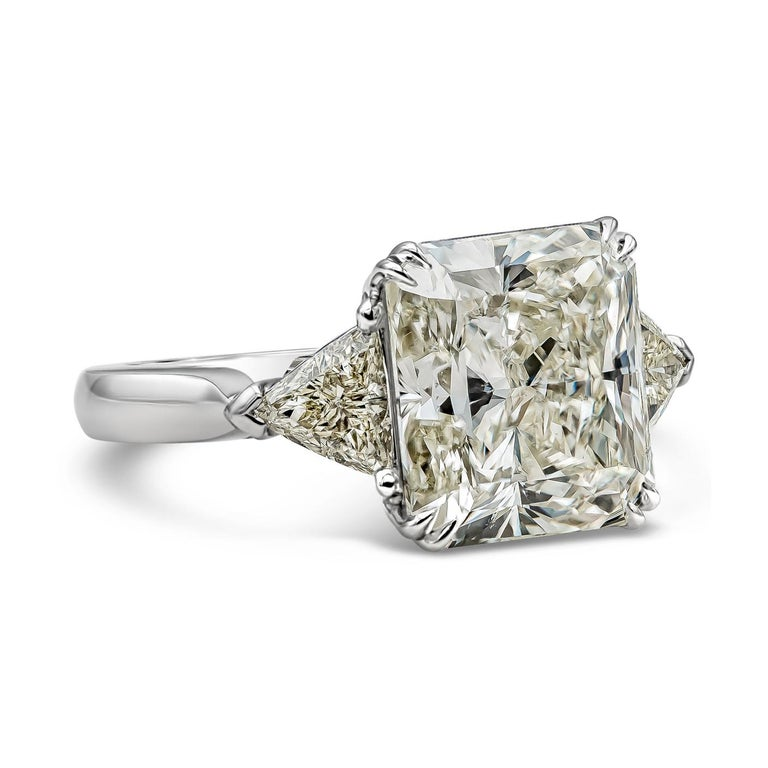Features a 7.41 carat radiant cut diamond certified by GIA as M color, SI1 clarity. Flanking the center diamond are trillion diamonds on either side. Side diamonds weigh 0.75 carats total. Hand-made in platinum.    Style available in different price