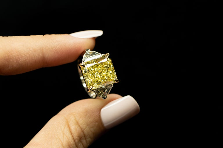 As yellow as the sun, a beautiful 8.11ct Radiant, Fancy Yellow, VVS2 Natural Diamond set in platinum & 18K yellow gold with 2 stunning Trapezoid cut natural diamonds=1.23cttw  This Diamond is GIA certified.