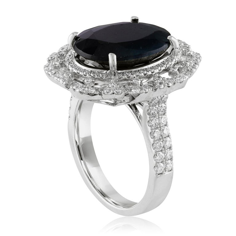 Beautiful Classic Oval Halo Ring. The ring is 18K White Gold. The center stone is an oval shaped 8.49 Carats Dark Greenish Blue Sapphire. The Sapphire is certified by GIA, Heated. The ring has 1.05 Carats in Diamonds F/G VS/SI. The top of the ring