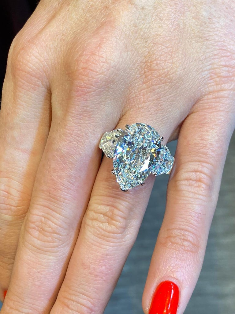 GIA Certified Pear Shape Diamond Three Stone Ring. 1 pear shape diamond along with 2 calf's head cut diamonds weighing 2.40 carats, set in platinum. Center Stone Weight: 8.73 Cts, H in color & VVS1 in clarity. Ring Size: 6.25 Resizable free of