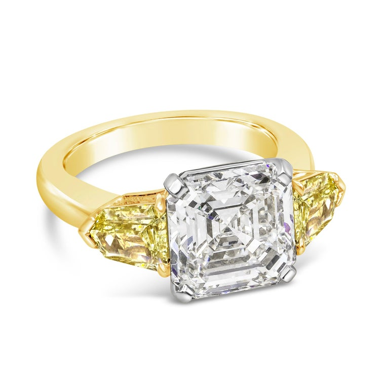 A unique engagement ring showcasing a 5.05 carat asscher cut diamond certified by GIA as G color, VS2 clarity. Center diamond is flanked by two color-rich yellow diamonds on either side. Accent diamonds weigh 0.81 carats total. Set in 18 karat
