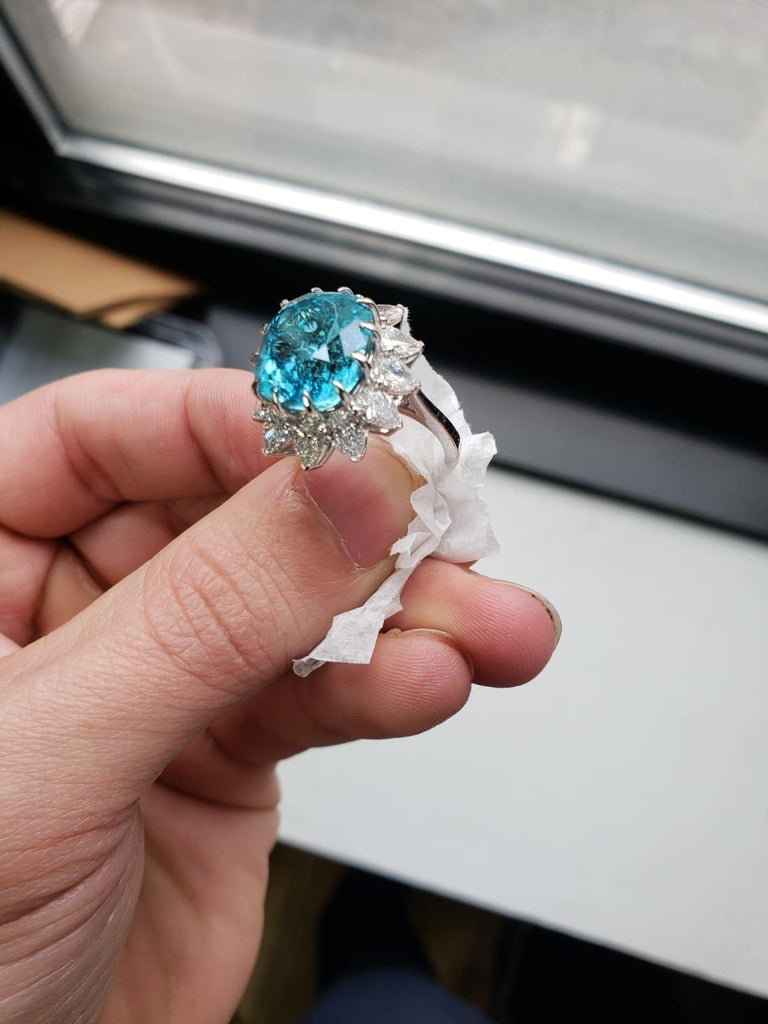 This stunning hand made ring has a superlative 8.25 carat cushion cut paraiba tourmaline that displays its brilliant aqua color in this contemporary and romantic ring.   Paraiba tourmalines are among the most exciting gemstones in the world, and