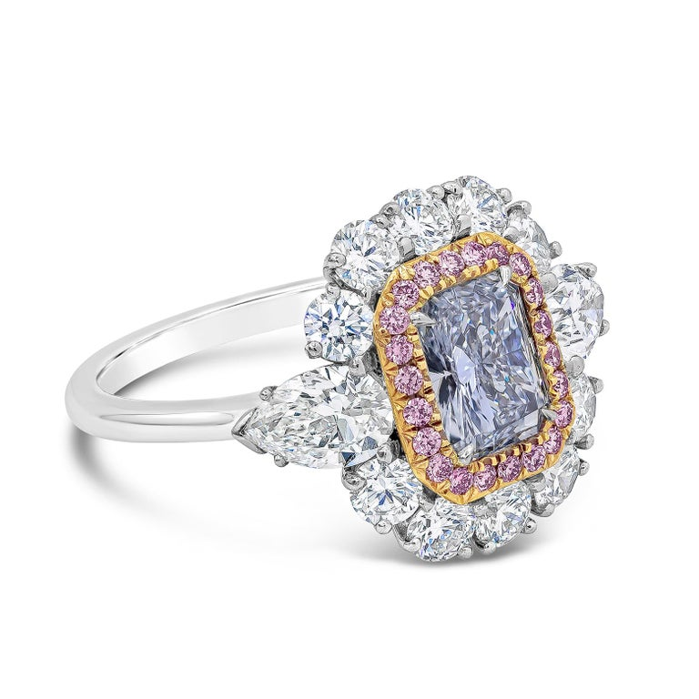 A color-rich and chic engagement ring showcasing a 1.09 carat blue diamond certified by GIA as Fancy Light Blue color, VS1 clarity. Surrounding the center is a row of pink and white diamonds in a polished platinum mounting. White diamonds are D-E