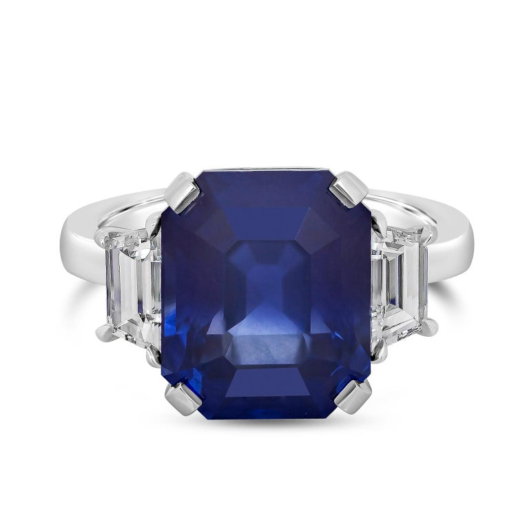 Showcasing an 8.99 carat GIA certified emerald cut blue sapphire, flanked by step-cut trapezoid diamonds, set in a polished platinum mounting. Accent diamonds are 0.76 carats total and are approximately E color, VS clarity.   Style available in