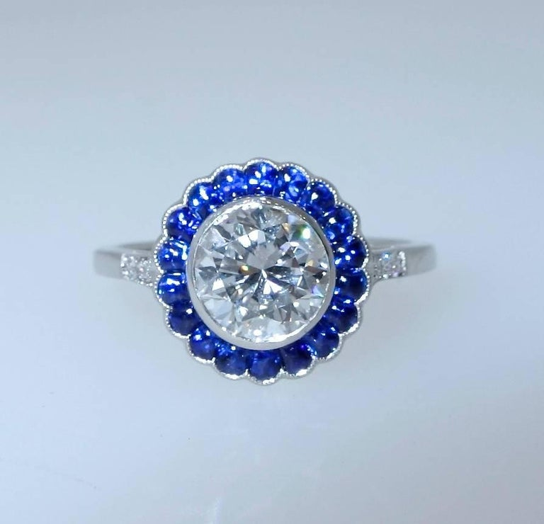 1.21 ct round brilliant cut diamond, GIA certified F (colorless) and slightly included to the first degree (SI1).  The bright blue natural sapphires surrounding this well cut diamond are all well matched and a bright blue.  The ring is platinum and