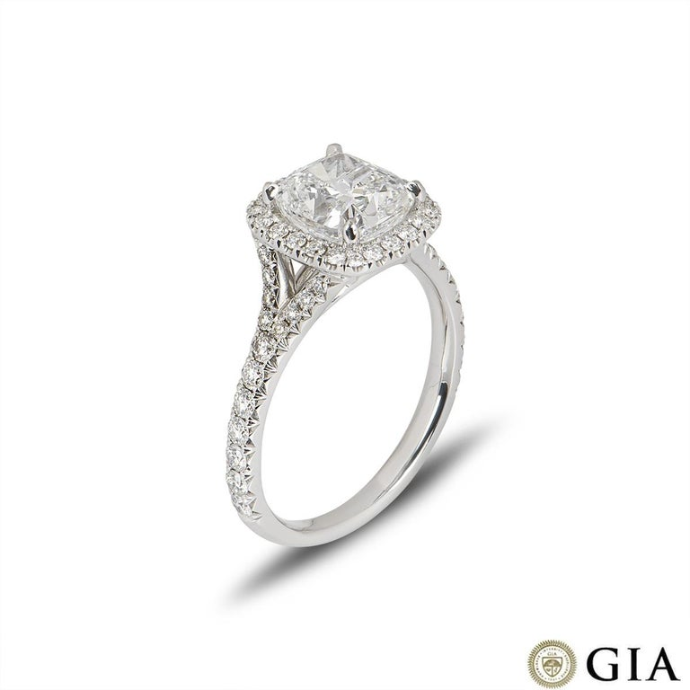 A stunning white gold cushion cut diamond engagement ring. The ring comprises of a cushion cut diamond in a halo setting with a weight of 2.14ct, F in colour and VS1 clarity. The round brilliant diamonds in the halo setting have a total weight of