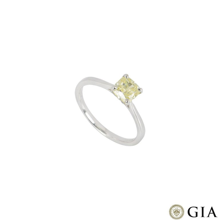 A platinum cushion cut fancy yellow diamond ring. The ring features a cushion cut diamond set to centre in a four claw setting. The diamond has a weight of 1.01ct with a fancy yellow colour with even distribution and SI1 clarity. The ring is