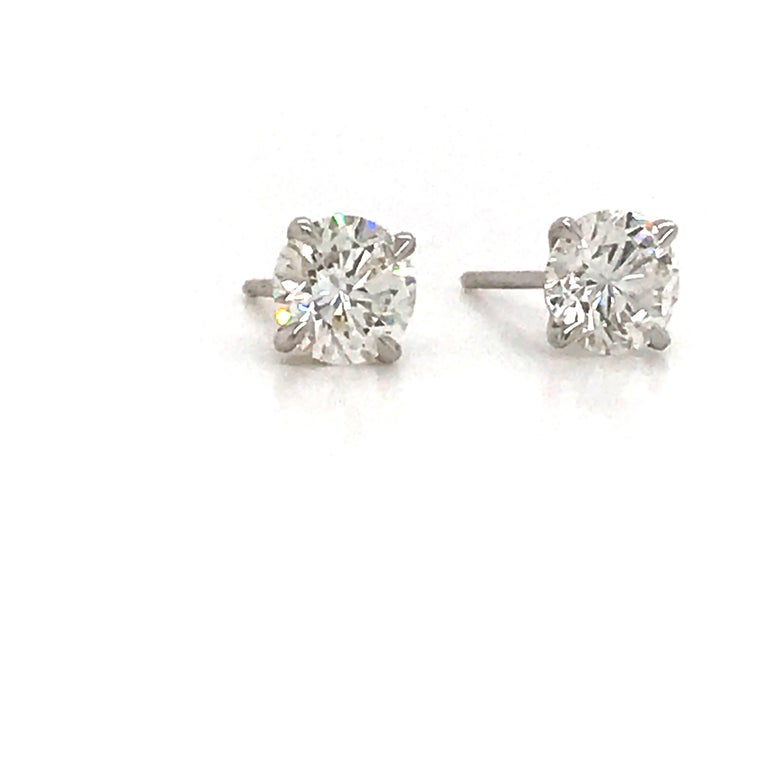 GIA Certified diamond stud earrings weighing 1.40 carats in a 14k white gold 4 prong martini setting. Color H-I Clarity: VS2-SI1