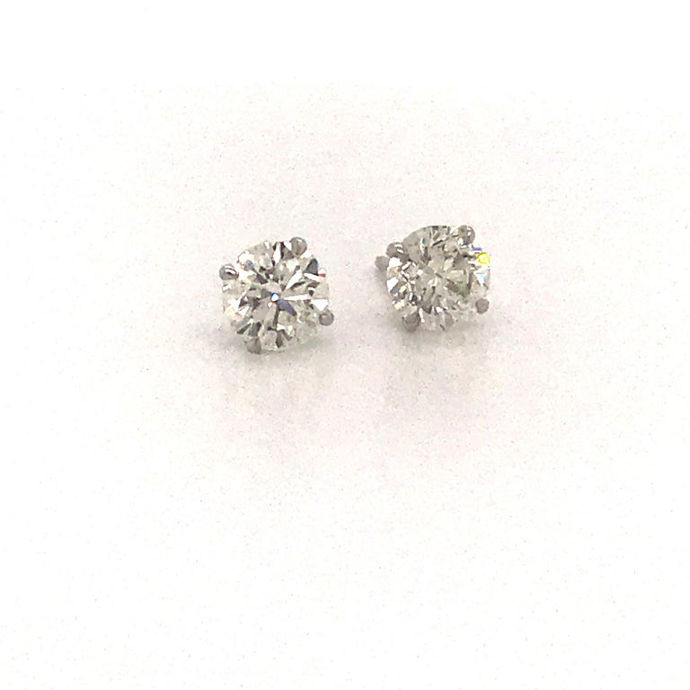GIA Certified diamond stud earrings weighing 2.02 carats in a 4 prong champagne setting. Color H Clarity SI2-I1  Brilliant Cut Stones Eye Clean