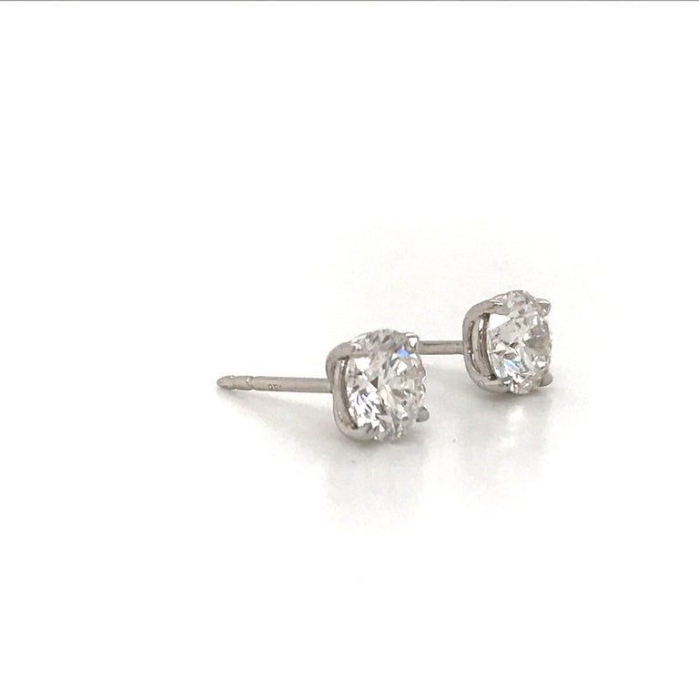 GIA Certified diamond stud earrings weighing 2.04 carats in a 4 prong champagne setting, 18k white gold. Color G Clarity I1