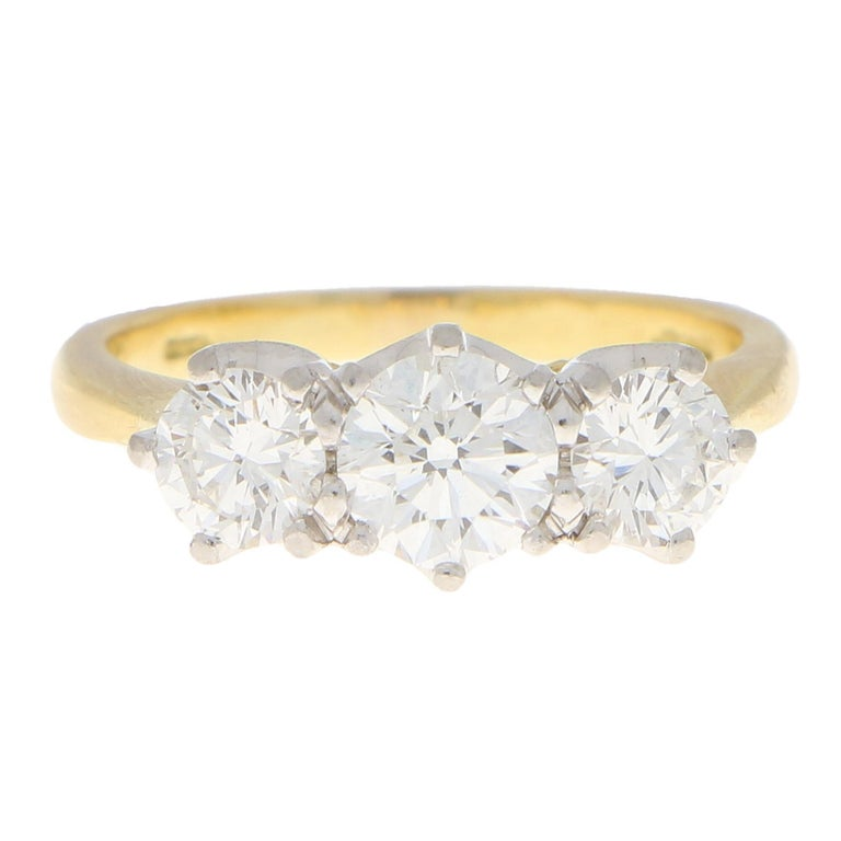 A beautiful certified diamond three stone engagement ring set in 18k yellow gold.  The ring is centrally set with a lovely 0.70 carat round brilliant cut diamond which is six-claw set to centre. This is then sided by a 0.35 and a 0.36 round