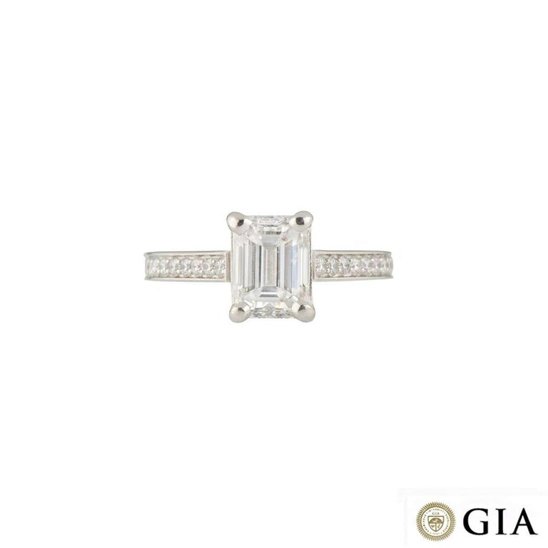 A beautiful diamond platinum engagement ring. The ring comprises of a emerald cut diamond with a weight of 1.51ct, F colour and VVS2 clarity in a 4 claw setting. Complementing this centre diamond are 9 round brilliant cut diamonds on each shoulder