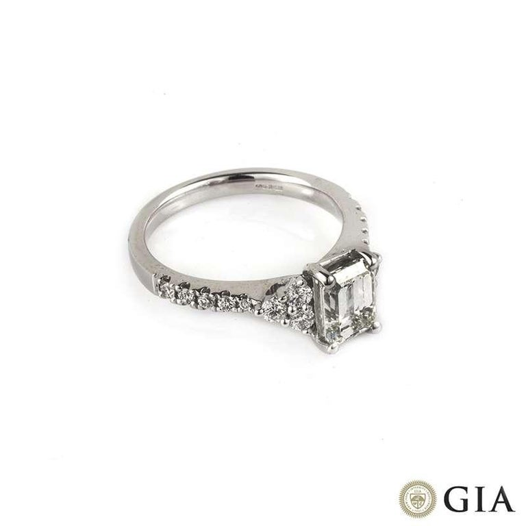 An emerald cut diamond ring in 18k white gold. The central 1.33ct diamond is G colour, VS1 clarity and is set between a cluster of 3 round brilliant cut diamonds on each side, along with diamond set shoulders totalling 0.37ct. The ring is currently