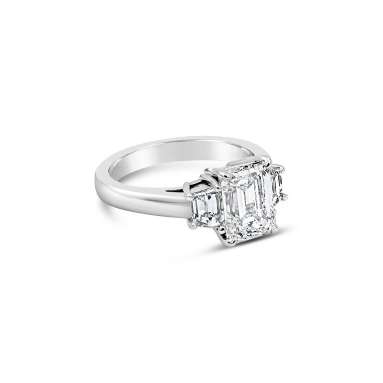 A simple and timeless engagement ring design showcasing a 2.12 carat emerald cut diamond certified by GIA as G color, VS2 clarity. Flanking the center are step-cut trapezoid diamonds weighing 0.69 carats total. Set in a platinum mounting.  Style