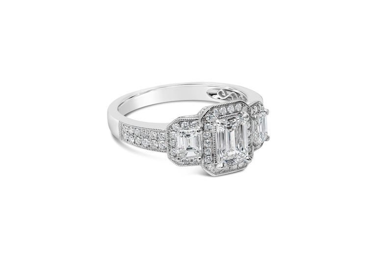 An antique-style engagement ring showcasing a 0.75 carat emerald cut diamond certified by GIA as H color, VVS1 clarity. Flanking the center diamond are two emerald cut diamonds set in a round brilliant diamond halo. Accent diamonds weigh 0.78 carats
