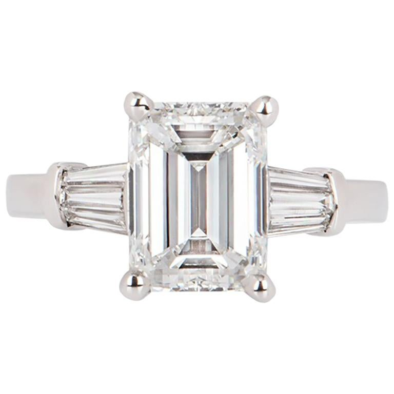 A stunning white gold emerald cut diamond ring. The emerald cut diamond is set within a four claw setting and weighs 3.02ct, G colour and VVS2 in clarity. The central diamond is flanked on either side with 3 tapered baguette cut diamonds, totalling