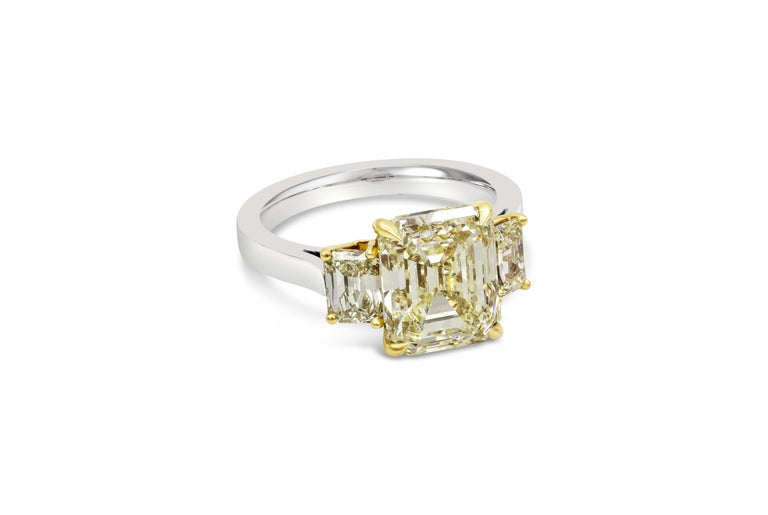 A simple and sophisticated three-stone ring design showcasing a 5.17 carat emerald cut yellow diamond certified by GIA as Fancy Yellow color, VS1 clarity. Flanking the center are yellow emerlad cut diamonds on either side; weighing 1.17 carats