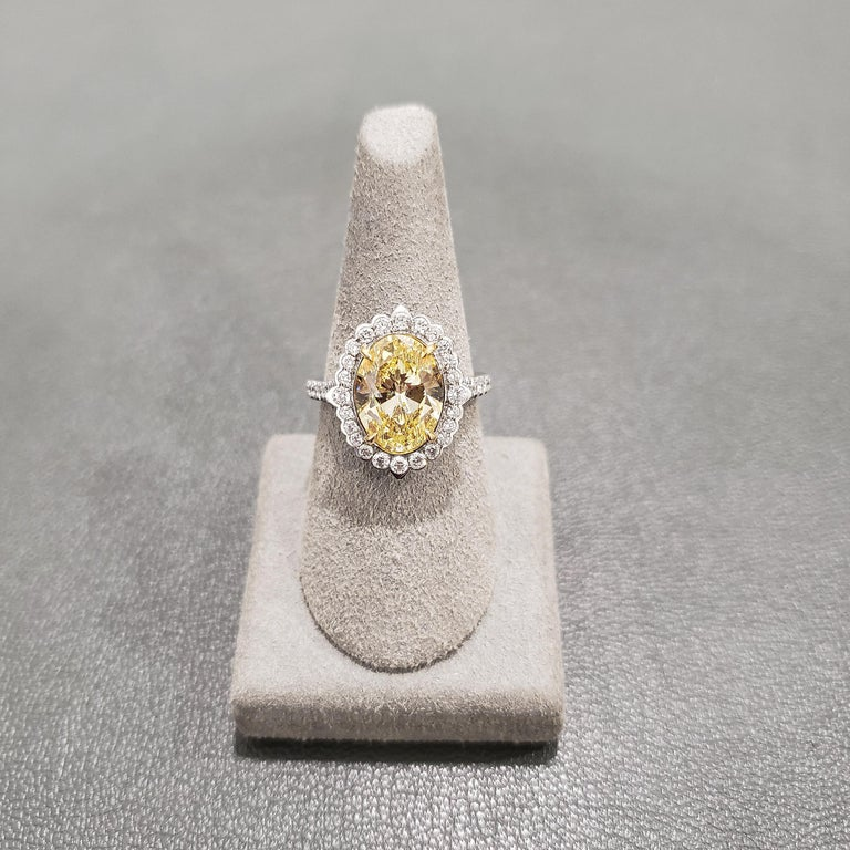 GIA Certified 3.39 Carat Fancy Intense Yellow color and SI1 clarity diamond center stone. A single row of round brilliant diamonds bezel set around the center stone. Row diamonds are also set on either side of the ring. Made in Platinum and 18k