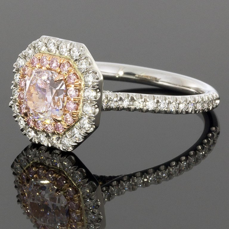 This one-of-a-kind, custom made ring features a cushion cut, GIA certified, Fancy pink diamond center. This rare gem is surrounded by an inner halo of natural pink diamonds set in rose gold & an outer halo of white diamonds set in platinum. The
