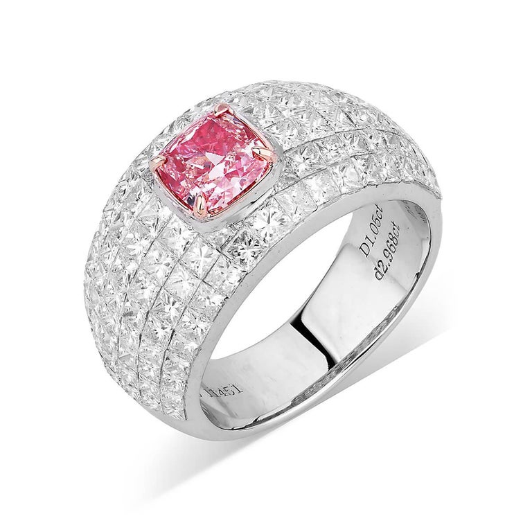 This piece consists of a natural untreated 1.05 fancy pink main diamond completely surrounded by smaller natural white diamonds, making up a total of 4.02 Carats. This piece has been expertly crafted using 18 Karat White Gold. Cushion Shape.
