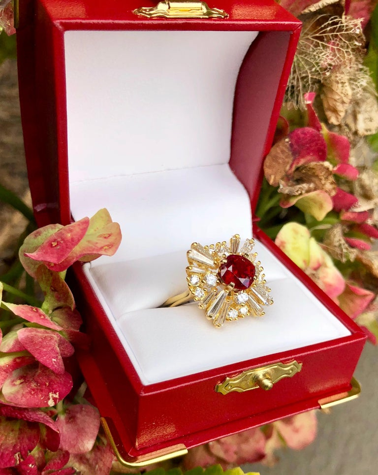 Cushion cut natural corundum ruby is GIA certified, prong set in 18 karat yellow gold and surrounded by prong-set tapered baguette and round diamonds in a timeless ballerina-style cocktail ring.  Transparent red ruby measures 6.85 mm x 6.80 mm x