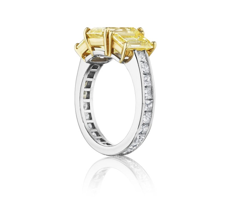 A ring centered by three slightly graduating prong-set, emerald-cut fancy intense yellow diamonds, offset by a channel set band of princess-cut diamonds; mounted in 18K yellow gold and platinum • 3 emerald-cut yellow diamonds, weighing 1.06, 1.02,