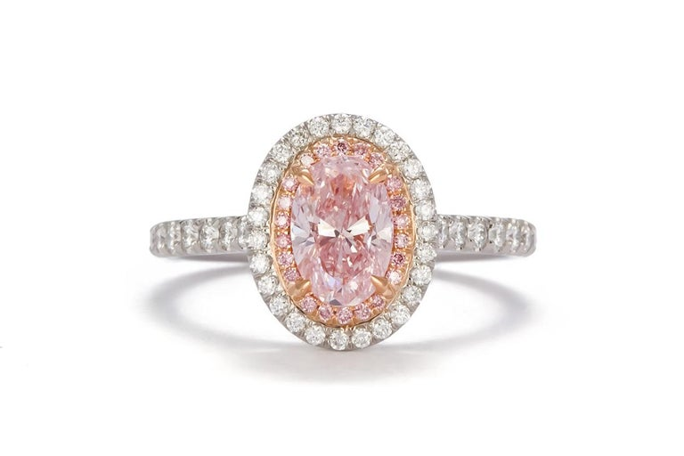 We are pleased to present this brand new 1.58ctw fancy pink oval diamond halo ring. This beautiful piece was custom designed in house and crafted from the finest materials. It features a GIA certified and laser inscribed 1.11ct natural fancy pink