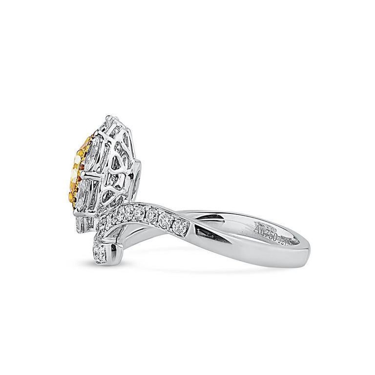 This incredible piece hosts a centre 0.79 carat cushion shape fancy yellow natural untreated diamond. It is beautifully complimented by smaller natural white and yellow diamonds making up a total carat weight of 1.86. This piece has been expertly