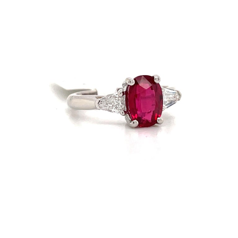 GIA Certified three stone ring featuring one oval shape red Ruby weighing 2.01 carats flanked with two bullets weighing 0.41 carats, crafted in Platinum.