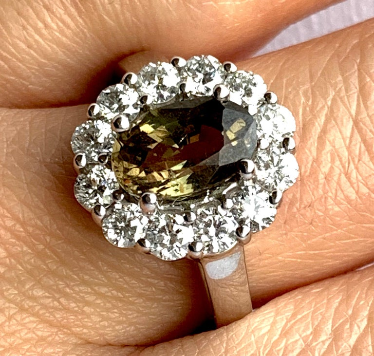 This GIA Certified Alexandrite is truly a special stone. Changing color in light, the 2.23 carat stone ranges from yellowish green to brown-yellow. Surrounded by petals of brilliant white diamonds totaling 0.61 carats, this is a piece you don't want