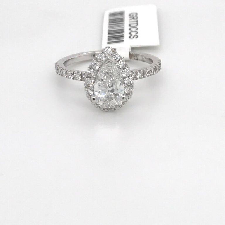 14K White gold engagement ring featuring one pear cut diamond weighing 1.01 carats flanked with a diamond halo setting weighing 0.38 carats. GIA Certfied E, SI1