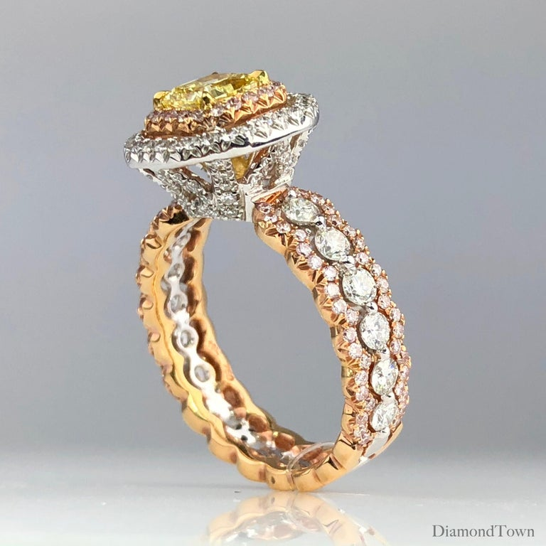 This stunning ring features a 0.63 carat GIA certified Natural Fancy Intense Yellow center, surrounded by a double halo of round diamonds, set in 18k White, Yellow, and Rose Gold.  The middle halo is set in a rose gold accent, which is featured