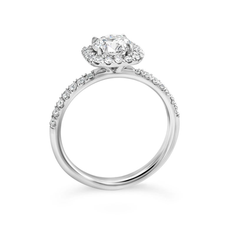 A chic engagement ring style showcasing a 1.01 carat round brilliant diamond certified by GIA as F color, SI2 clarity, set in a cushion halo accented with round diamonds. Accent diamonds weigh 0.44 carats total. Made in platinum.  Style available in
