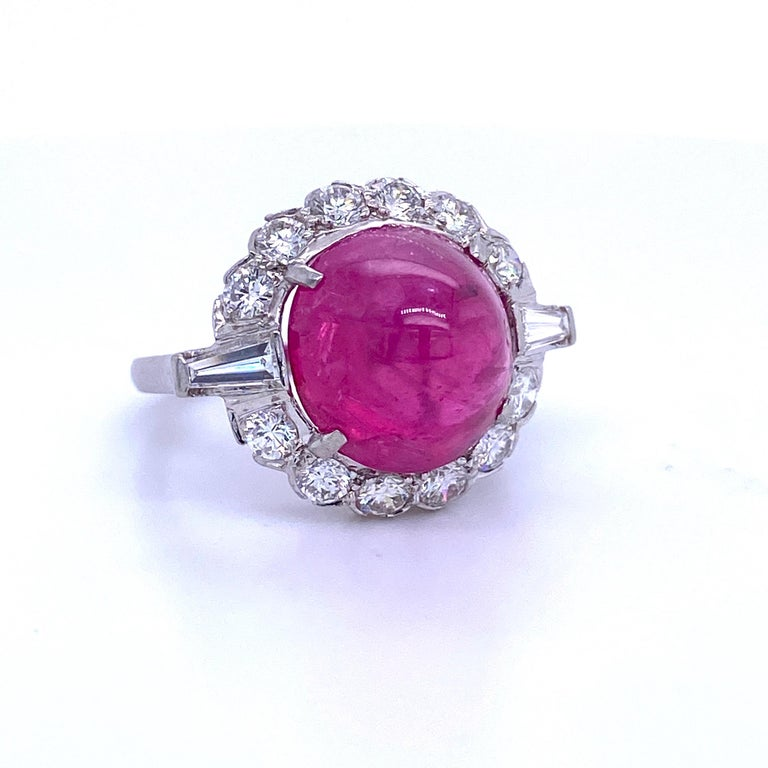 Platinum cocktail ring featuring one GIA Certified Sugar Loaf Ruby weighing 10.42 carats flanked with round brilliants and baguettes weighing 1.50 carats. No Heat! Color G Clarity SI