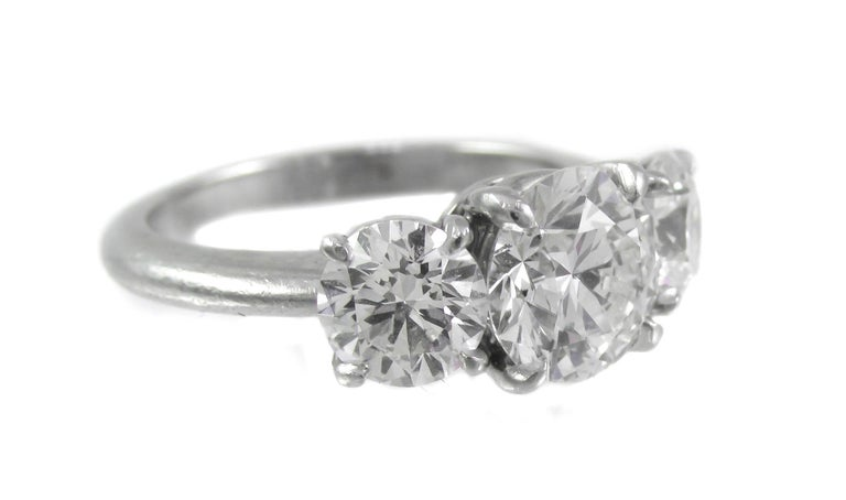 Beautifully hand crafted platinum 3 stone diamond ring, set with 3 perfectly matched round brilliant cut diamonds.The center diamond weighing 1.55 carats is complimented by 2 side stones weighing 0.71 and 0.70 carats, angled ever so slightly as not