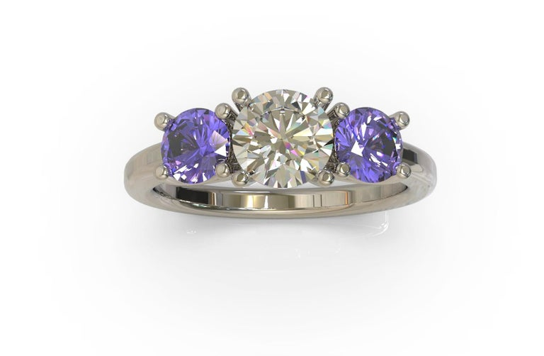 Ring with a trio of gemstones  Centrally set within a round brilliant cut  diamond displays a beautiful vitreous lustre. Two purplish blue Ceylon sapphires are similarly set on either side. Simply gorgeous. Round brilliant cut diamond:  1= D colour,