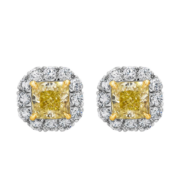 Features two brilliant radiant cut yellow diamonds weighing 1.45 carats total, surrounded by a row of round brilliant diamonds. Each yellow diamond accompanied by GIA report stating that the diamonds are fancy yellow color, VS1 and VS2 clarity.
