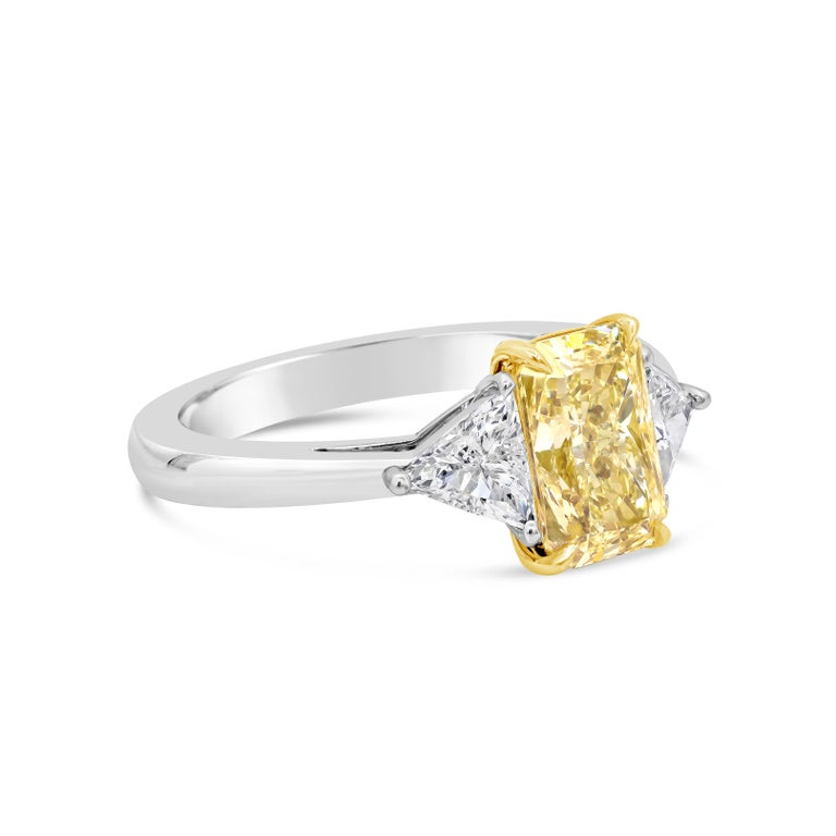 This platinum engagement ring showcases a gorgeous 2.02 carat elongated radiant cut diamond set in a four prong 18 karat yellow gold basket. GIA certified the center diamond as Fancy Yellow color, I1 clarity. Flanking the center are brilliant