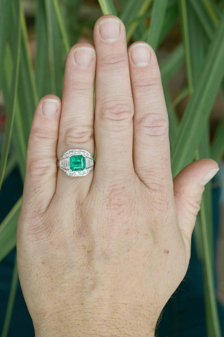 A sublime, certified GIA certified Colombian emerald engagement ring. This authentic, antique Art Deco masterpiece makes for a dynamic statement cocktail ring. Centered by a 2.40 carat step cut of a lush, vivid grass-green, it appears with such