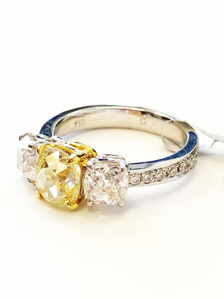 Gorgeous sunshine fancy yellow cushion weighing 1.45 carats with 1.63 carats of good quality white diamond rounds.  Handmade mounting in 18k two tone gold in size 6.  Beautiful ring with GIA certificate.