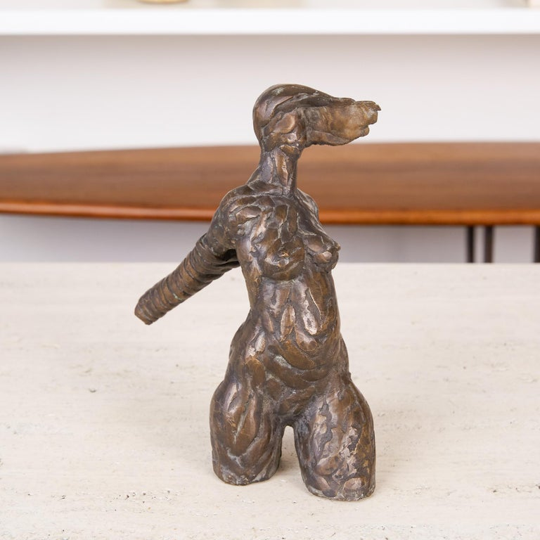 Bronze figurative sculpture in the style of Alberto Giacometti. This cast sculpture consists of a textured bronze female form, starting from her mid-thigh up to the top of the subjects head. Her arms are bound together behind her and her hair is