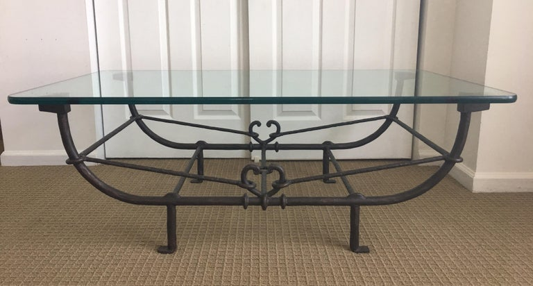 Large Gorgeous Sculptural Metal coffee table with a thick glass top. The frame/base is a heavy metal in a bronzed wrought iron tone finish featuring hand hammered textured detailing in rods, stretchers, crossbars and posts. The unique frame features