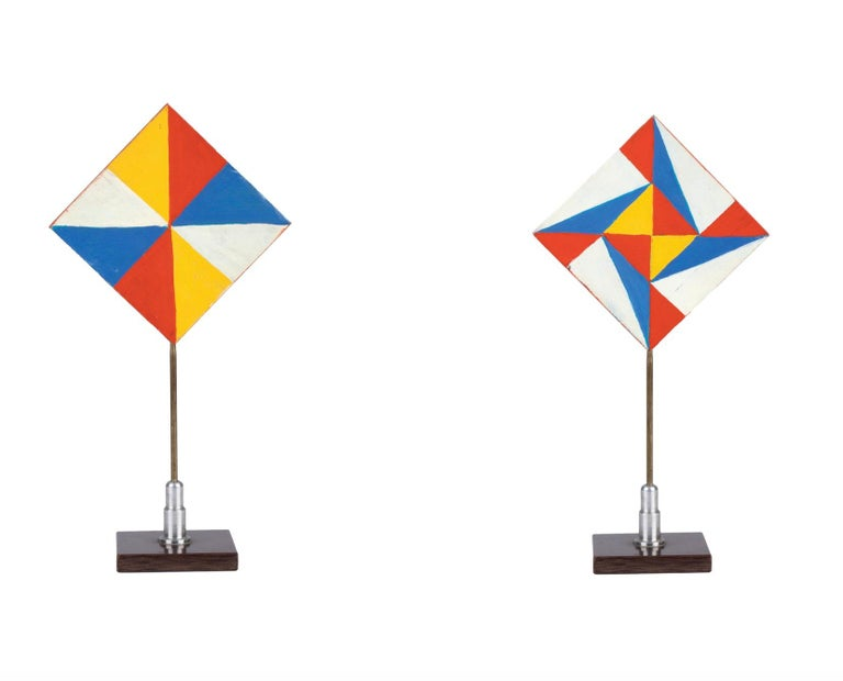 The 'Colorful Triangles'  by Giacomo Balla (1871-1958), geometric pattern with red, blue, yellow and white triangles down and up (recto and verso), realized in the 1930s.  Tempera on wood, aluminium structure and plastic base, 21,5 x 10,7 cm (23 x