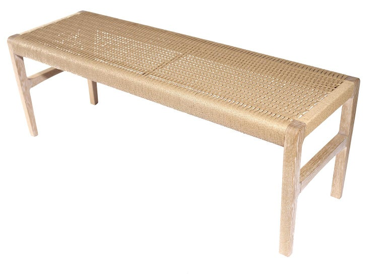 """A bench with subtle curves in cerused white oak with woven Danish cord seat, perfect for use in the bedroom, hallway, living space or kitchen. Measures: Seat 59""""."""
